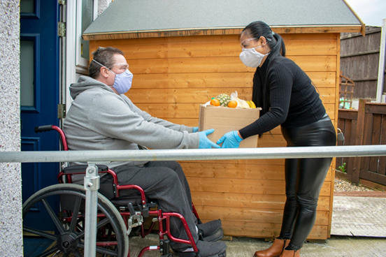Image Description: Man in wheelchair receives box of supplies at front door - both are wearing mask over their mouth and nose.