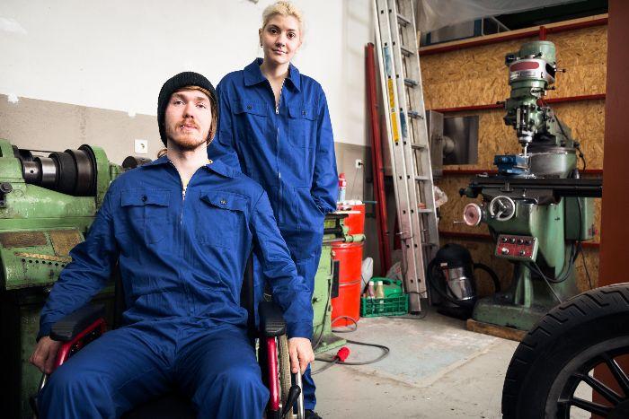 In mechanics' garage man in wheelchair with female coworker