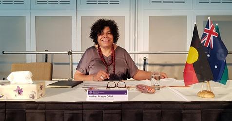 Commissioner Andrea Mason sits behind desk smiling