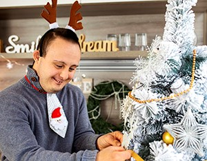 Young person with disability decorate a Christmas tree